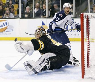 Winnipeg Jets' Kyle Wellwood watches as his shot deflects off the glove of Boston Bruins' Tuukka Rask during the first period of a game in Boston today.