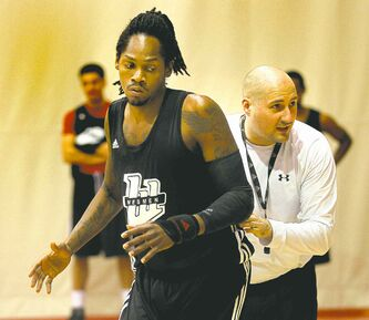 Wesmen coach Mike Raiimbault shows forward Steven Wesley how he wants it done at practice Tuesday.
