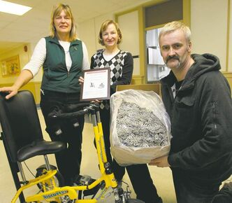 George Klassen holds part of 113 kilograms of can tabs his late sister, Barbara Klassen, collected. He gave them to a Seven Oaks School Division  committee that collects them to help the disabled. Physiotherapist Sandy Loewen (left) and committee rep Carol Anandranistakis give a certificate of thanks.