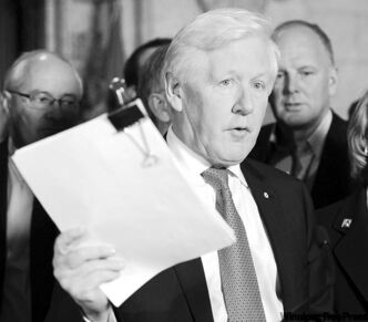Bob Rae holds up a signed petition in reaction to Harper's suggestion of pension changes.