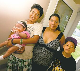 Eugenia Flores stands in her Brandon home with her daughter, Lindsay, and stepsons Vidal, left, and Jesus.
