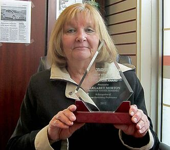 Frontier Toyota sales rep Margaret Morton with award for being top-selling sales rep in Pattison Auto Group.