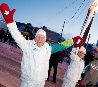 Eddie 'the Eagle' Edwards (top) passes the Olympic flame to Jennine Thaddeus along its run in Winnipeg Thursday.