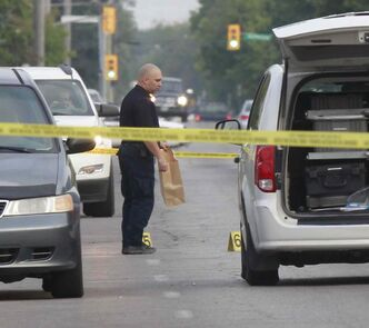 A Winnipeg police officer gathers evidence on Selkirk Avenue Tuesday morning after a man was assaulted on the street at about 1:30 a.m.