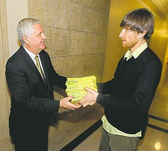 Eric Reder (right) presents Conservation Minister Gord Mackintosh with 836 cards calling on the  government to ban peat mining in Manitoba.