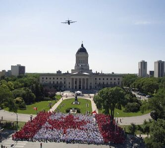 Thousands of Winnipeggers form a living flag at the Manitoba legislature as a Hercules aircraft passes overhead.