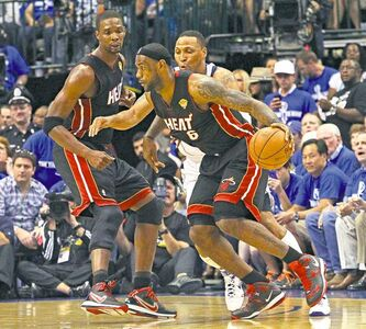 Miami Heat's LeBron James, right, drives against Dallas Mavericks' Shawn Marion during the first quarter of Game 5 of an NBA basketball finals, Thursday, June 9, 2011, in Dallas. Heat's Chris Bosh watches at left. (AP Photo/El Nuevo Herald, Hector Gabino)
