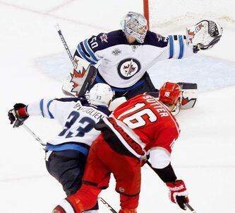 Winnipeg Jets goaltender Chris Mason and teammate Dustin Byfuglien combine to stymie Carolina Hurricanes' Brandon Sutter in the third period.