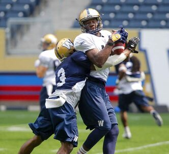 Chris Matthews No. 13 catches the ball while Cauchy Muamba, No. 3 rushes in during Winnipeg Blue Bombers practice Wednesday.