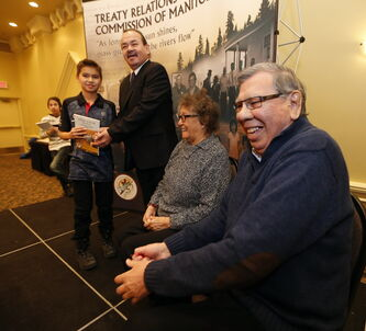 Elders Harry Bone and Doris Pratt share a laugh as Chief Morris Swan Shannacappo presents Joshua Wilson, 9, and Kyle Courchene, 13, (stepping on stage) copies of Untuwe Pi Kin He — Who We Are.