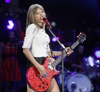 Taylor Swift straps on the guitar Saturday.
