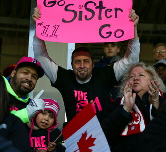 Desiree Scott's family watches Desiree play for Canada for the first time. Brother Nick Scott (from left), foster sister Charlie, brother Christopher Hawkins and mother Charlene Gusberti watch Desiree (left, No. 11) on Thursday.