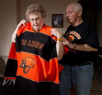 Ray Brittain, right, helps his wife Jenny into her B.C. Lions poncho before posing for a photograph at their home in New Westminster, B.C., on Monday November 12, 2012. Regardless of whether their home team is in the final, CFL fans are universally game for a celebration come Grey Cup time. Whether they're settling in at home or hitting the road to take in the festivities in person, league boosters are ready to mark the occasion in style. THE CANADIAN PRESS/Darryl Dyck