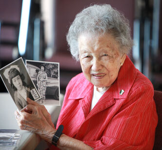 """Winifred """"Winnie"""" Paktong holds photos of her when she was 12 and 24 at her retirement home."""