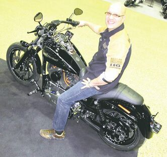 Keni Harvey, sales manager at Lone Star Harley-Davidson, with a Dyna model the dealership customized.