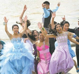 Some Sisler High School grads whoop it up along the Red River Friday before the formal graduation dinner.