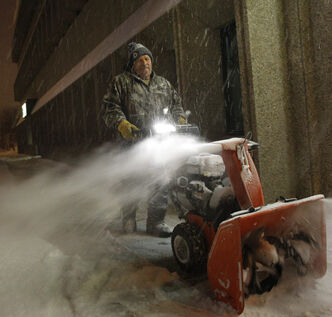 Omer Lacoursiere clears the snow around the Carpathia Credit Union on Main Street early this morning. this was his first job of the day and he expects a busy day ahead with more snow expected to fall today.