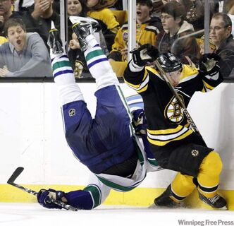 Boston Bruins' Brad Marchand, right, trips Vancouver Canucks' Sami Salo, left, in the second period of an NHL hockey game in Boston, Saturday, Jan. 7. Bruins general Manager Peter Chiarelli is angered after Marchand was suspended five games by the NHL for this hit.
