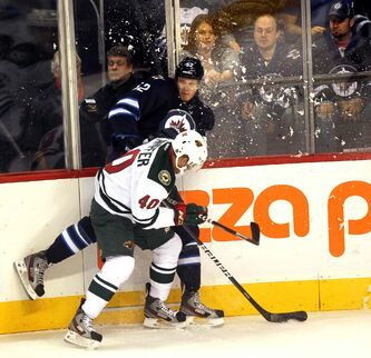 Ivan Telegin of the Winnipeg Jets collides with Steven Kampfer of the Minnesota Wild during the first period of Thursday night's game.