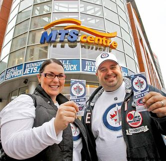 Ian Buckingham and his wife, Ami, show off their tickets outside the MTS Centre Tuesday.