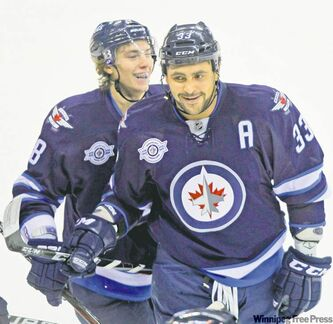 Dustin Byfuglien (in front of teammate Alexander Burmistrov) is all smiles after lighting the lamp in the first period Monday night at the MTS Centre.