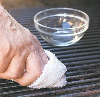 Oil and a towel are used to clean a grill.