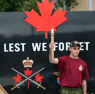 A soldier from CFB Shilo holds the baton high in front of a statue that reads: