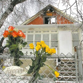 On Friday, flowers sit against the fence of a home on Hethrington Avenue, where the deadly fire broke out.