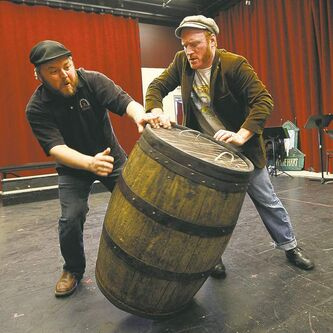 Cory Wojcik (left) and Carson Nattrass roll a barrel with a body inside during rehearsal.
