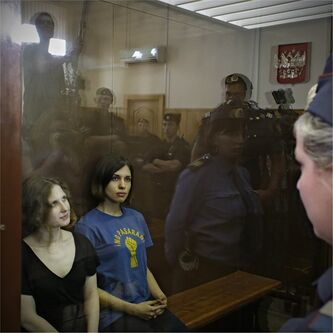 Feminist punk group Pussy Riot members, from left, Maria Alekhina and Nadezhda Tolokonnikova sit in a glass cage at a court room in Moscow, Russia on Friday, Aug. 17, 2012. A judge found three members of the provocative punk band Pussy Riot guilty of hooliganism on Friday, in a case that has drawn widespread international condemnation as an emblem of Russia's intolerance of dissent. T-shirt on right worn by Tolokonnikova is Spanish and translates to