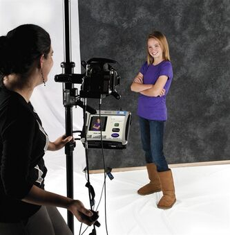 This 2013 publicity photo provided by Lifetouch School Photography shows a photographer taking a commercial picture of a model posing for a school photo for the Fall 2013 season. School picture day can be a success with some easy tips from photographers. Most important, they say, is helping your child feel comfortable with having their portrait taken. That means being relaxed, and wearing appropriate clothes in solid colors or simple patterns. (AP Photo/Lifetouch School Photography)