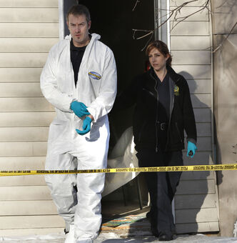 Winnipeg police at the scene Wednesday where a man was found dead in a suite in a rooming house on Balmoral Street on Tuesday.