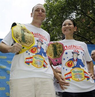 "FILE - In this July 3, 2012, file photo, hot-dog eating champions Joey Chestnut, left, and Sonya ""The Black Widow"" Thomas pose for photographers at City Hall Park in New York, following the weigh-in for contestants in the annual Coney Island Fourth of July international hot-dog eating contest. The pair aim to take the crowns again at the annual Fourth of July contest on Coney Island.(AP Photo/Kathy Willens, File)"