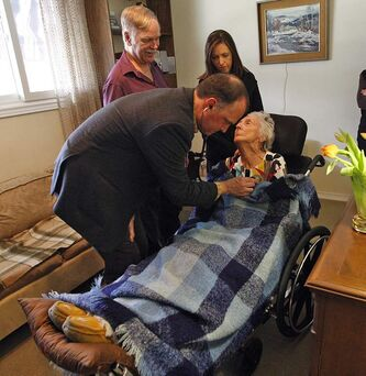 Dr. Sawchuk listens to Theresa Miller's heart during home visit. From left: Dr. Paul Sawchuk,  husband Don Miller, case co-ordinator Arle Jones, Theresa Miller.