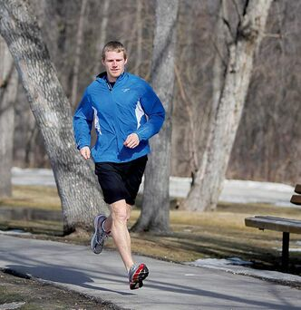 Corey Gallagher runs around the duck pond at St. Vital Park.