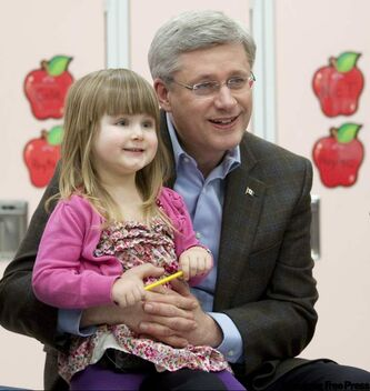 Prime Minister Stephen Harper holds Journey Benson, 3, at a school in Beaumont, Alta., Monday.