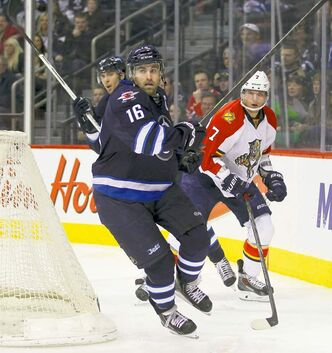 Winnipeg Jets captain Andrew Ladd wheels around Dmitry Kulikov behind the Panthers' net in the second period Thursday.