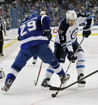 The Lightning's Brendan Mikkelson (29) tries to slow up the Jets' Kyle Wellwood in Tampa on Thursday.