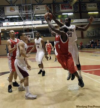Craig Sharpe (8) of the Winnipeg Wesmen is blocked by Sekani Milligen (21) of the Valley City State University Vikings during the Wesmen Classic Thursday. The Wesmen were defeated and shut out of the final.