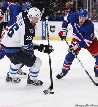 The Jets' Blake Wheeler (26) and the Rangers' Michael Del Zotto (4) vie for control of the puck during the first period of the game in New York on Tuesday.