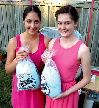 Miah (left) and Keana Wallwin show off some of their cotton candy after demonstrating their candy-making prowess in their backyard.