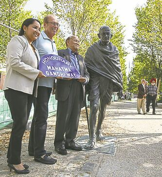 Devi Sharma (left), Sam Katz and Krishnamurti Dakshinamurti with a statue of Gandhi.