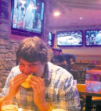 A patron at Tapp's Neighbourhood Pub in St. Vital enjoys a burger and a pint.