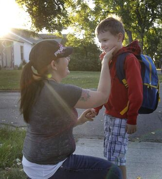 Six year old Dante Mowat with his mother Skie gets ready to take his first school bus trip to start grade one Wednesday morning.