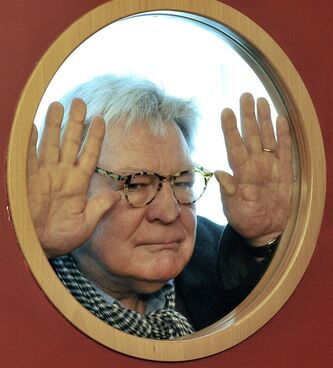 "File - British film director Alan Parker looks through a cinema door window prior to meeting the media in Prague in this Friday, March 28, 2008 file photo. Alan Parker, the much-lauded British director whose work includes ""Midnight Express,"" ""Fame"" and ""Mississippi Burning,"" is receiving the British Academy Film Awards' highest honor. The 68-year-old will collect the BAFTA Fellowship at the London ceremony next month. While known for being outspoken, Parker said Tuesday Jan. 22 2013, that he'll be"