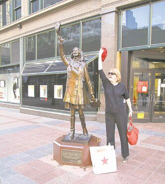 Julie Carl does her best Mary Tyler Moore impression beside the actress's statue at the site the opening scene for her iconic TV show was shot.