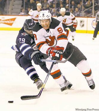 Jets' Johnny Oduya tries to keep  Devils' Dainius Zubrus off the disc in the contest Saturday.