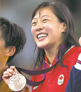 Canada's Carol Huynh shows off her bronze medal from 48kg Women's Freestyle Wrestling at the Olympic Games in London on Wednesday August 8, 2012.
