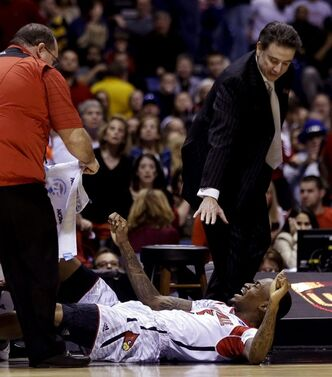 Louisville head coach Rick Pitino and trainers tend to injured guard Kevin Ware during the first half of the Midwest Regional final in the NCAA college basketball tournament against Duke, Sunday, March 31, 2013, in Indianapolis. Ware badly injured his lower right leg and had to be taken off the court on a stretcher. (AP Photo/Darron Cummings)