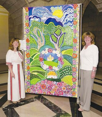 Erna Braun, MLA for Rossmere, joins Susan Zuk, President of the Manitoba Parents for Ukrainian Education (MPUE) with the beautiful quilt celebrating Taras Shevchenko's bicentennial, made by students from Springfield Heights School, Bernie Wolfe Community School and Chief Peguis Junior High.